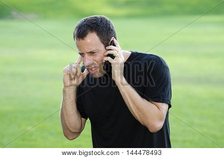 Man having a hard time hearing on his cell phone, bad connection.