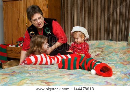 A grandmother reaches down as she strains with her tongue out to pull a Christmas stocking up onto a bed to help her granddaughters open gifts.