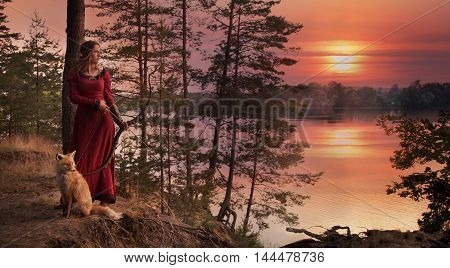 A young woman in medieval clothes with a bow and arrow stands beside the river with a Fox against the setting sun