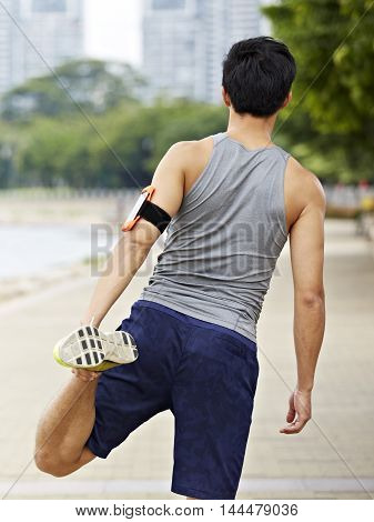 young asian male jogger with fitness tracker attached to arm warming up by stretching leg before running.
