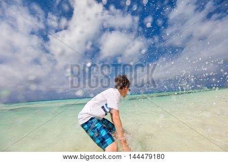 Teen age boy in sun protection rash guard at tropical beach on summer vacation