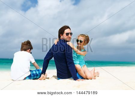 Father and kids enjoying summer beach vacation on tropical island