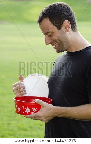 Excited man looking into Christmas container for treats.
