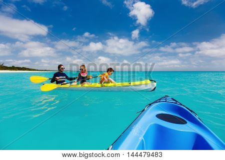 Family father and kids kayaking at tropical ocean water during summer vacation