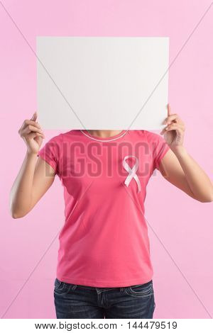 healthcare and medicine concept - woman with pink breast cancer awareness ribbon and a blank board