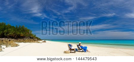 Back view of a young beautiful woman relaxing at white sand tropical beach panorama