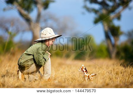Adorable little girl in South Africa safari with giraffe to