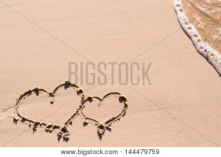 Hearts drawn on beach sand and sea wave