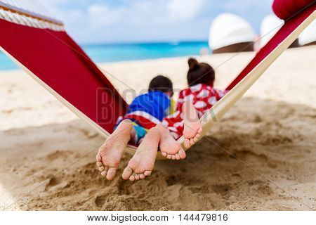 Brother and sister kids relaxing in hammock at tropical beach