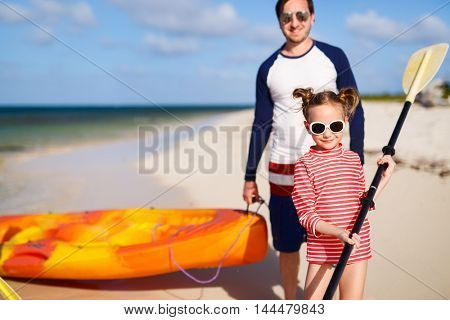 Family father and daughter pulling colorful kayaks after paddling at tropical ocean water during summer vacation