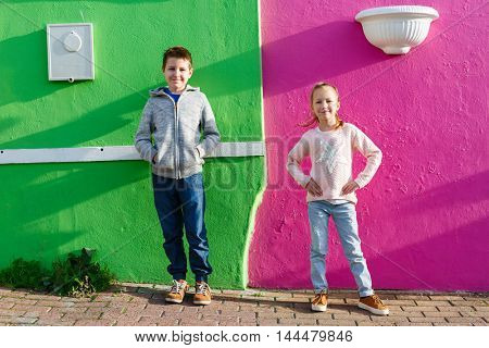 Two kids boy and girl outdoors against colorful house in Bo Kaap Quarter in Cape Town