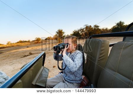 Adorable little girl in South Africa safari on morning game drive in open vehicle