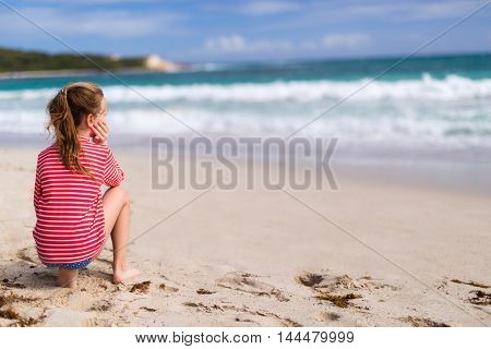 Back view of adorable little girl at beach during summer vacation
