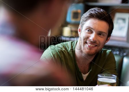 people, leisure, friendship and communication concept - happy man with friend drinking beer at bar or pub