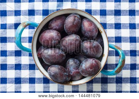 Fresh plums from garden in old pot on checkered tablecloth. Top view.