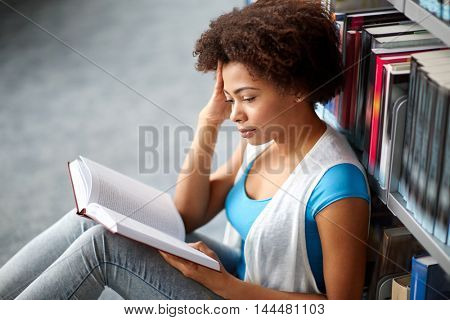education, high school, university, learning and people concept - african american student girl reading book sitting on floor at library