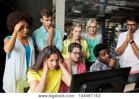 people, education, technology, fail and school concept - group of international students with computers at library in university having some problem