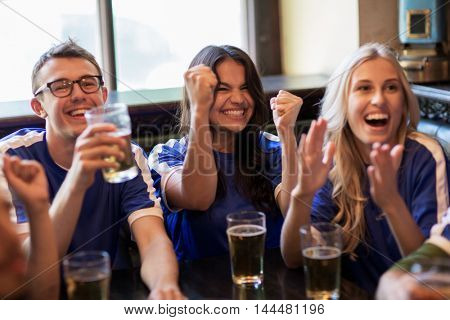 sport, people, leisure, friendship and entertainment concept - happy football fans or friends with beer watching game and celebrating victory at bar or pub