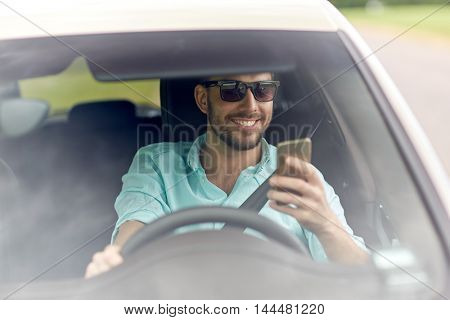 road trip, transport, travel, technology and people concept - happy smiling man in sunglasses driving car with smartphone
