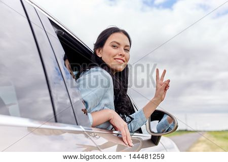 summer vacation, holidays, travel, road trip and people concept - happy young woman driving in car and showing peace sign
