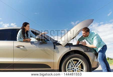 road trip, transport, travel and people concept - family couple with open hood of broken car at countryside