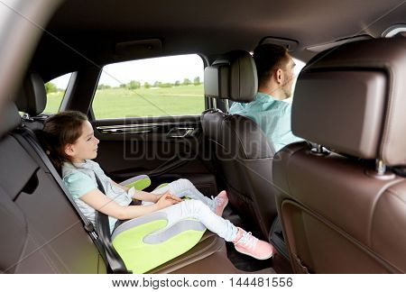 family, transport, road trip and people concept - happy little girl in safety seat driving in car with her dad