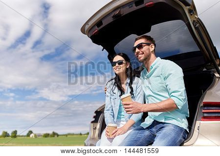 travel, summer vacation, road trip, leisure and people concept - happy couple drinking coffee from disposable cups sitting on trunk of hatchback car outdoors