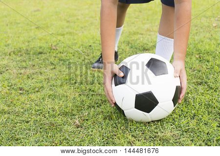 Child is keeping football on green grass.Close up