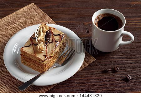 Cup of hot coffee and delicious honey cake with cream on brown wooden table