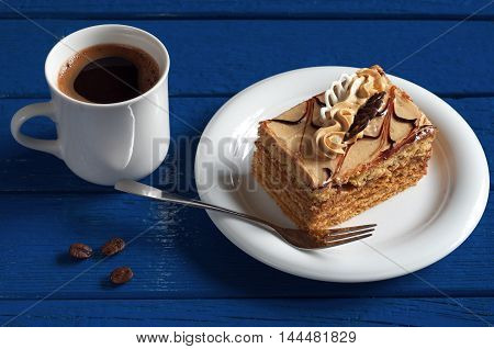 Cup of hot coffee and honey cake with cream on dark blue wooden table