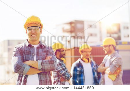 business, building, construction and people concept - group of smiling builders in hardhats outdoors