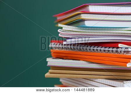 Stacked school notebooks on blackboard background