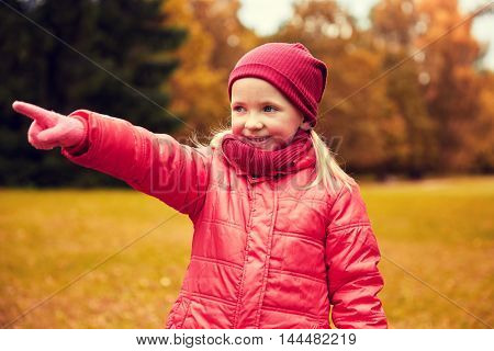 autumn, childhood, leisure, gesture and people concept - happy little girl pointing finger to something in autumn park