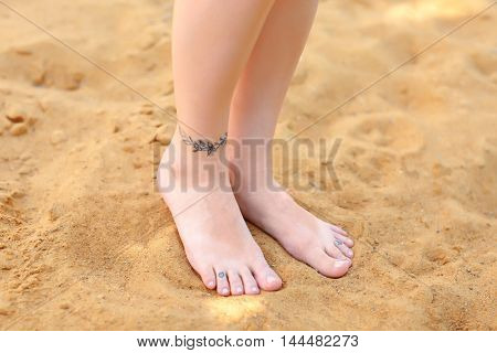 Female legs with tattoos on sand