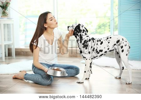 Female owner feeding her dalmatian dog