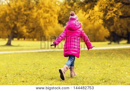 season, childhood, activity, motion and people concept - happy little girl running in autumn park from back
