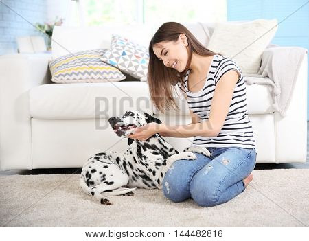Owner with her dalmatian dog sitting on a carpet