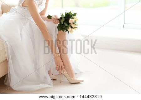 Bride in a beautiful wedding dress with bouquet of flowers putting on shoes