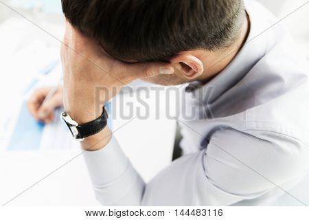 business, people, fail, paperwork and technology concept - close up of businessman with laptop computer and papers working in office