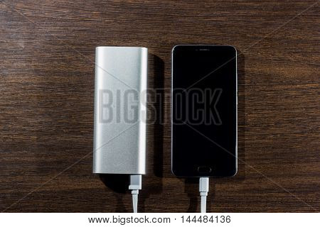 Smartphone charging with power bank on dark wood board