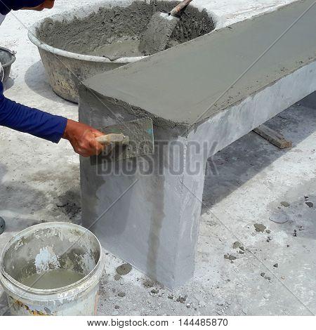 workman using hand trowel to smooth wet concrete over a new park bench, Samila Beach, Thailand