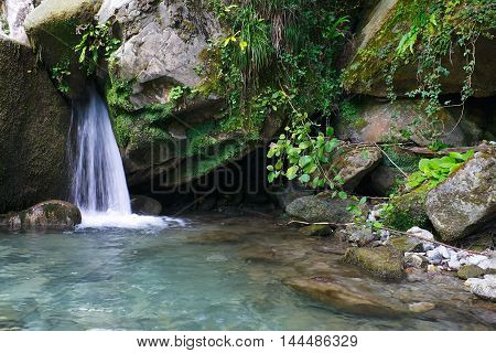 Little marvellous waterfall among the rocks in a mountain forest
