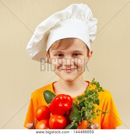 Little smiling chef with the fresh vegetables