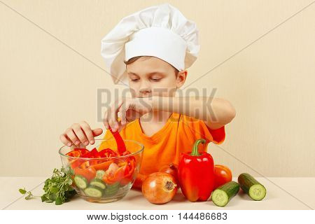 Young chef puts chopped vegetables for a salad in a bowl