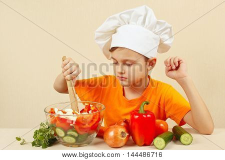 Young chef mixing the vegetables in a bowl with salad