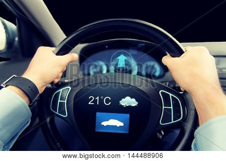 transport, business trip, technology and people concept - close up of male hands holding car wheel and driving with weather sensor on board computer screen