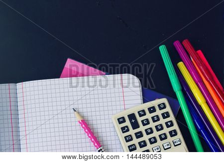 School supplies - notebook, calculator, pens on the chalkboard