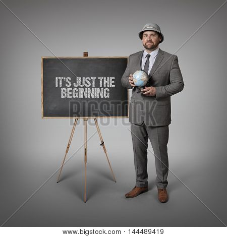 Its just the beginning text on blackboard with businessman holding globe in hands