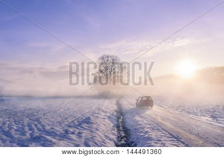 Car silhouette through fog on a winter morning - Winter image with the silhouette of a car driving on a snowy country road through mist and the sunrise light.