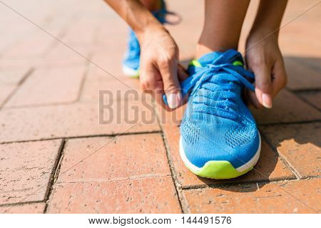 Woman trying shoelace and get ready to run